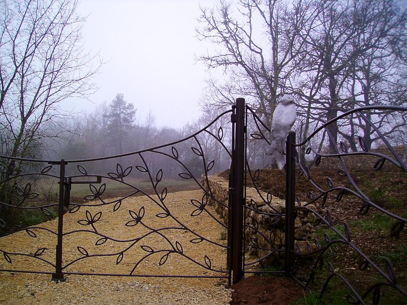 Ici un travail en fer forgé et inox clôture et portail de jardin avec motif végétal.
