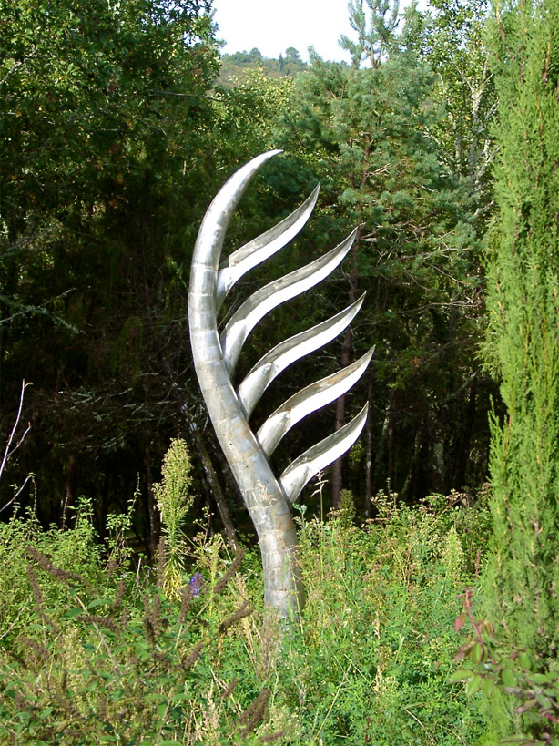 Inspired by a palm tree , this sculpture in stainless steel graces the wilds around an otherwise very ordered garden