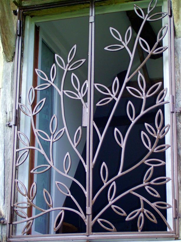 Le motif du feuillage pour cette grille ouvrante s'intègre parfaitement dans une maison traditionnelle de campagne