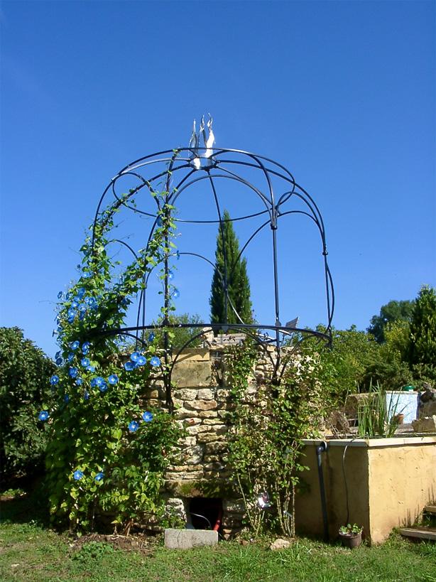 Pergola de jardin couronnée d'une création en inox.